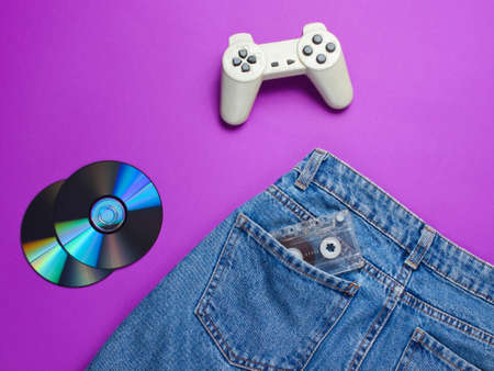 Pop culture gadgets from the 80s on the purple paper surface. Retro gamepad, Cd's, audiotape in denim jeans pocket