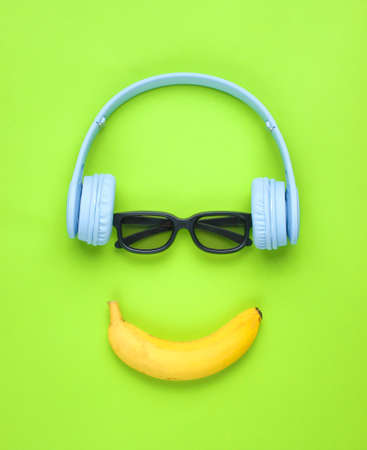 Minimalism flat lay concept. Smiling face listens to music Headphones, 3D glasses, banana on a green background.