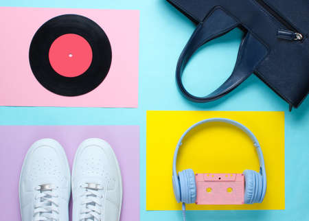Pop Culture, retro 80s old fashioned objects on a creative background. White sneakers, headphones with audio cassette, lp record, women's leather bag. Top view. Flat lay.