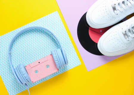 Pop Culture, retro 80s old fashioned objects on a creative background. White sneakers, headphones with audio cassette, lp record. Top view. Flat lay.