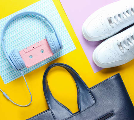 Retro 80s old fashioned objects on a creative background. White sneakers, headphones with audio cassette, women's leather bag. Top view. Flat lay.
