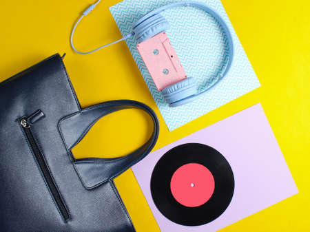 Retro 80s old fashioned objects on a creative background. Headphones with audio cassette, lp record, women's leather bag. Top view. Flat lay.