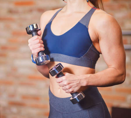 Muscular woman with perfect body in sportswear holding dumbbells in the gym against the brick wall.