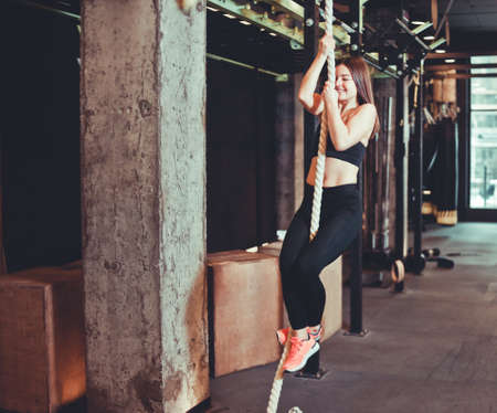 Fit girl climbing up the rope at the gym. Young strong woman performing gymnastics workout. Climbing exercise.