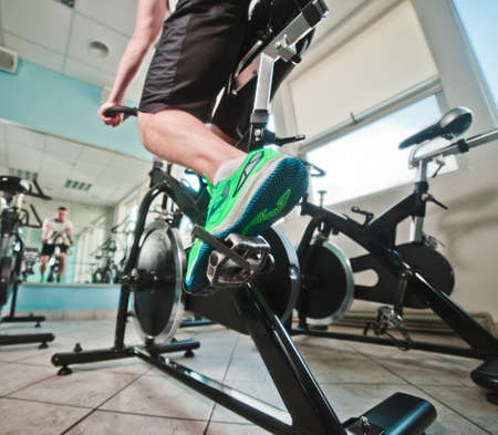 Wide angle view of man in sports sneakers and shorts does exercises on cardio bike at spinning class. Healthy lifestyle concept