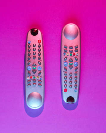 Retro wave style two tv remote with neon pink blue light. Top view