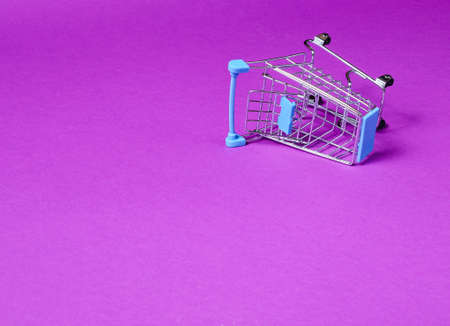 Minimalist shopping concept. Empty inverted miniature shopping trolley on purple background. Copy space