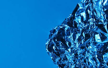 Crumpled Foil on a blue background with neon light