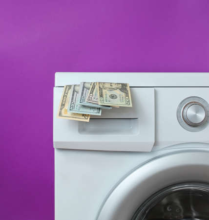 Dollar bills in the washing machine against purple background. Expensive wash concept