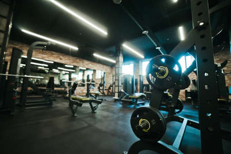 Gym equipment. Dark Gym with barbells on rack. Fitness workout center. Sport concept. Stock Photo