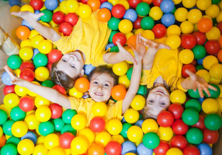 Three happy little kids girls in ball pit smiling happily at camera while having fun in children play center. Top view Banco de Imagens