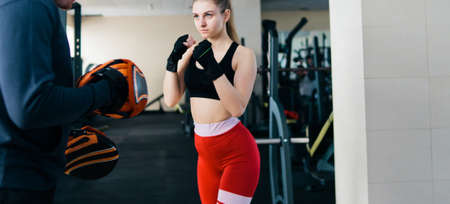 Young female boxing at gym with male instructor. Couple exercising punching Banco de Imagens