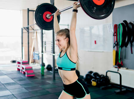 Strong athletic woman lifts a barbell over her head in the gym. Banco de Imagens