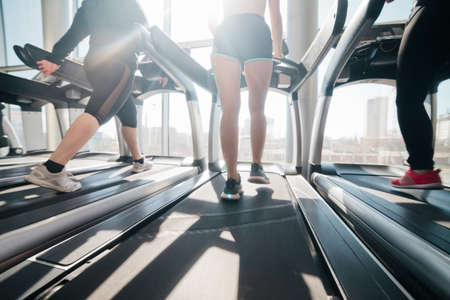 Cropped photo of female legs in sportswear and sneakers running on a treadmill in the gym against the window Banco de Imagens
