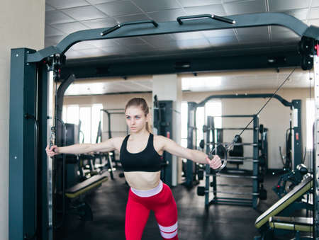 Blond fit woman doing exercise in crossover machine at gym