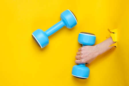 Female hand is holding blue plastic dumbbell through torn yellow paper. Minimalistic sport concept Banque d'images