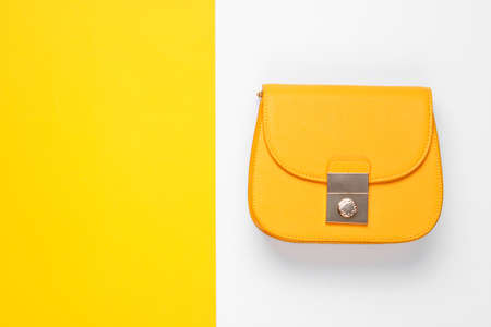 Leather yellow bag on a colored background. Top view, minimalism