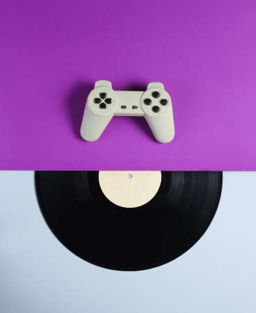 Gamepad, vinyl record on a purple gray background. Retro style. Top view