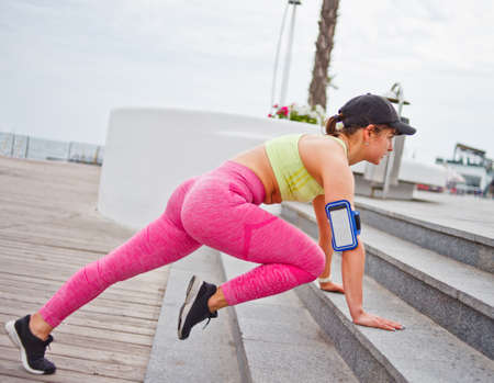 Cheerful fit woman in sportswear and cap doing push-ups from the stairs outdoors. Functional street workout.