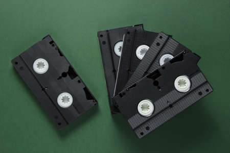 Stack of retro video cassettes on green background. Top view