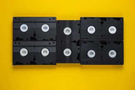 A lot of video tapes on yellow background. Top view