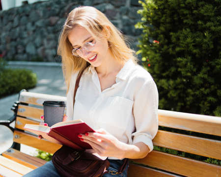 Young attractive blond female student student reading a book while sitting on a bench outdoors