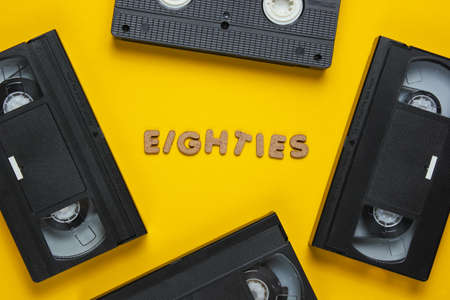 Retro style concept, 80s. Video cassettes on a yellow background with the word Eighties from wooden letters. Top view, minimalism