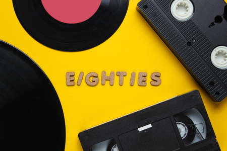 Retro style concept, 80s. Video cassette and vinyl records on yellow background with the word Eighties from wooden letters. Top view, minimalism Banque d'images