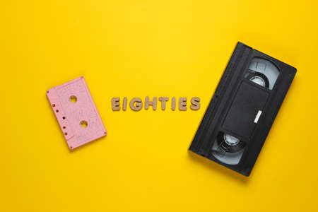 Creative retro style concept, 80s. Audio and video cassette on yellow background with the word Eighties from wooden letters. Top view, minimalism