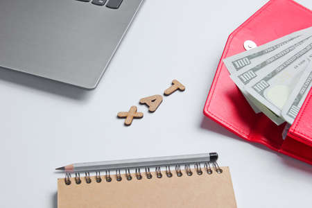 Creative business concept. Laptop, notebook,  pencil, wallet with dollar bills on white background with the word tax of wooden letters, minimalism