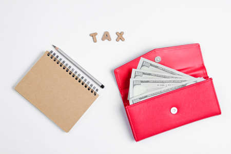 Creative business concept. Notebook, pencil, wallet with dollar bills on white background with the word tax of wooden letters, minimalism Banque d'images