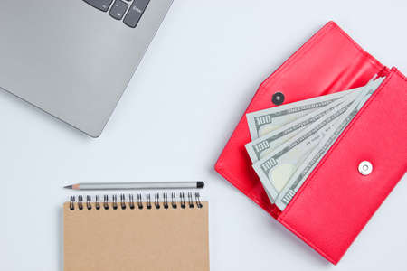 Creative business concept. Laptop, notebook,  pencil, wallet with dollar bills on white background, minimalism