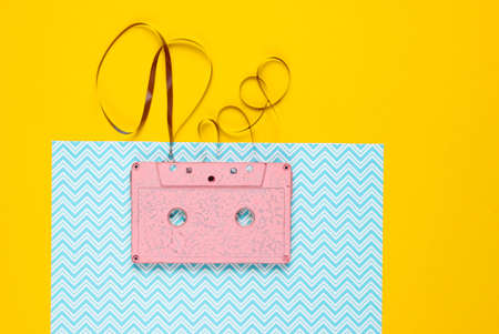 Music lover minimalism concept. Retro style 80s. Pink audio cassette with film on a blue yellow paper background.