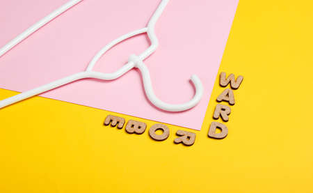 White hanger on yellow pink background with word wardrobe. Top view