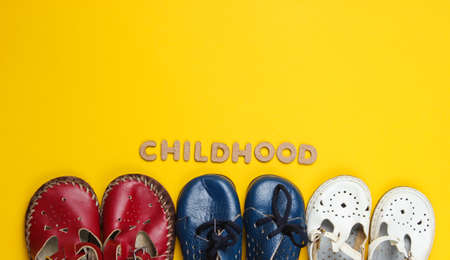 Lot of children's leather shoes on a yellow background with word childhood. Top view