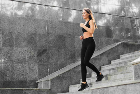 Fit woman in sportswear runs on the marble stairs outdoor. Morning running. Healthy lifestyle concept