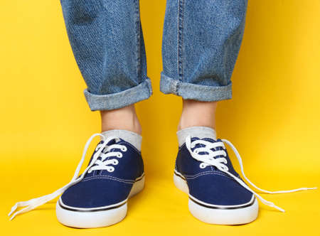 Fashion studio shot. Female legs in jeans and sneakers with untied laces on yellow background.
