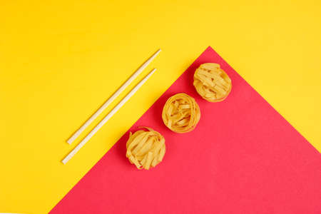 FeRaw tagliatelle noodles and chopsticks on yellow red paper background. Minimalistic food concept. Top view