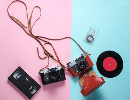 Retro top view still life. Vinyl record, vintage film camera, video and audio cassette on blue pink pastel background. Flat lay. Top view