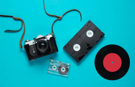 Retro top view still life. Vinyl record, vintage film camera, video and audio cassette on blue background. Flat lay