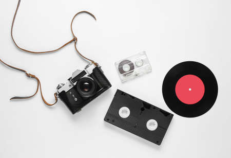 Retro top view still life. Vinyl record, vintage film camera, video and audio cassette on white background. Flat lay