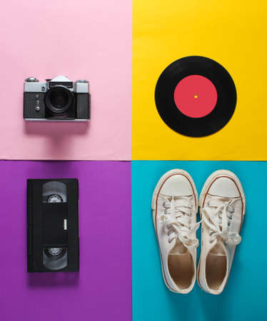 Retro still life. Old fashioned sneakers, vinyl record, vintage film camera, video cassette on colored background. Top view. Pop art flat lay