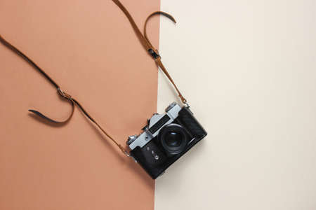 Vintage retro style film camera in leather cover with strap on brown background. Top view 免版税图像