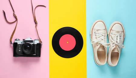 Retro still life. Old fashioned sneakers, vinyl record, vintage film camera on colored background. Top view. Pop art flat lay