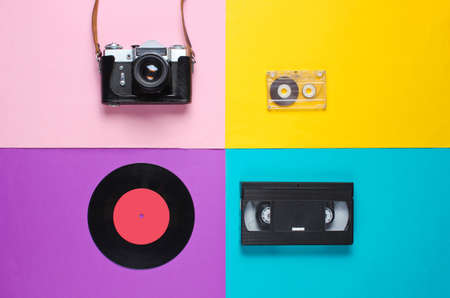 Retro top view still life. Vinyl record, vintage film camera, video and audio cassette on blue background. Flat lay. Pop art