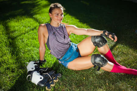 Young woman in protective gear and roller skates rest in the park on the grass. The concept of outdoor activities. Hobby. Sport lifestyle