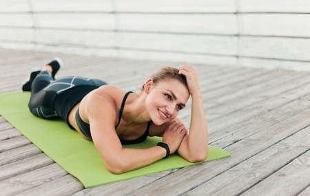 Portret Young fit woman in sportswear lying on a mat on a wooden terrace on the beach. Healthy lifestyle concept