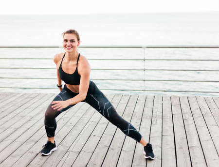Young sport woman lunges on the beach terrace Standard-Bild