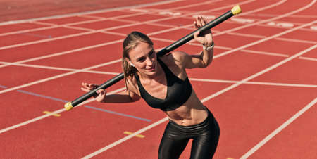 Young athletic woman in sportswear doing exercise with gymnastic stick on stadium track at bright sunny day