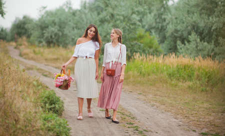 Two cheerful young women in retro style clothes are walking along the landing with a picnic basket and talking. Joint walk in nature